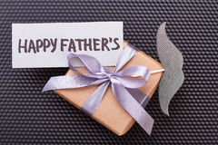 Father`s Day card on gift. Mustache, present box, black backdrop. Father will be happy Stock Photos
