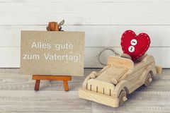 Father`s Day card with miniature easel and a wooden car.  German. Greeting `Alles gute zum Vatertag!`, which means `Happy Father`s Day Stock Photography