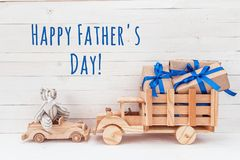 Father`s Day card. Wooden car with toy bear and wooden truck wit. H gifts. Happy Father`s Day royalty free stock image