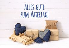 Father`s Day card with wooden toy car, gift boxes and denim hear. Ts. German greeting `Alles gute zum Vatertag!`, which means `Happy Father`s Day Royalty Free Stock Image