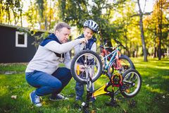 Father`s day Caucasian dad and 5 year old son in the backyard near the house on the green grass on the lawn repairing a bicycle,. Pumping a bicycle wheel. Dad royalty free stock photo