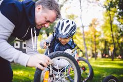 Father`s day Caucasian dad and 5 year old son in the backyard near the house on the green grass on the lawn repairing a. Bicycle, pumping a bicycle wheel. Dad royalty free stock image