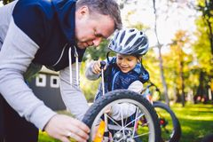 Father`s day Caucasian dad and 5 year old son in the backyard near the house on the green grass on the lawn repairing a bicycle,. Pumping a bicycle wheel. Dad stock photography