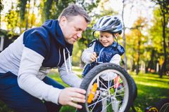 Father`s day Caucasian dad and 5 year old son in the backyard near the house on the green grass on the lawn repairing a bicycle,. Pumping a bicycle wheel. Dad stock image