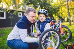 Father`s day Caucasian dad and 5 year old son in the backyard near the house on the green grass on the lawn repairing a bicycle,. Pumping a bicycle wheel. Dad royalty free stock image