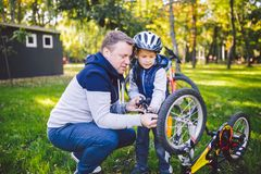 Father`s day Caucasian dad and 5 year old son in the backyard near the house on the green grass on the lawn repairing a bicycle,. Pumping a bicycle wheel. Dad royalty free stock photography