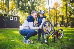 Father`s day Caucasian dad and 5 year old son in the backyard near the house on the green grass on the lawn repairing a bicycle,. Pumping a bicycle wheel. Dad royalty free stock images
