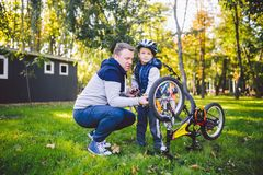Father`s day Caucasian dad and 5 year old son in the backyard near the house on the green grass on the lawn repairing a bicycle,. Pumping a bicycle wheel. Dad stock photos