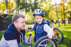Father`s day Caucasian dad and 5 year old son in the backyard near the house on the green grass on the lawn repairing a bicycle,. Pumping a bicycle wheel. Dad stock images