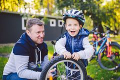 Father`s day Caucasian dad and 5 year old son in the backyard near the house on the green grass on the lawn repairing a bicycle, royalty free stock photography