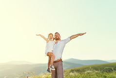 Father`s day. child daughter  in the arms of her dad outdoors on Stock Image