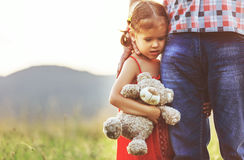 Father`s day. Child girl hugging father in nature at sunset. In summer stock photo