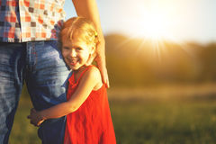 Father`s day. Child girl hugging father in nature at sunset. In summer stock photos