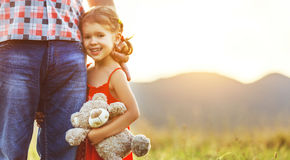 Father`s day. Child girl hugging father in nature at sunset. In summer royalty free stock photography