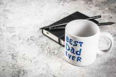 Father`s Day concept. Background for congratulating cards with a cup with the inscription Best Father ever, business notebook and pencils. copy space Stock Photography