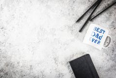 Father`s Day concept. Background for congratulating cards with a cup with the inscription Best Father ever, business notebook and pencils. copy space top view Royalty Free Stock Image