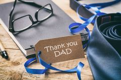 Blue tie, text thank you dad on the tag, office desk background stock photo