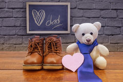 Father`s day concept. Brown shoes son with white teddy bear and blue necktie on rustic wooden background, father`s day concept stock photography