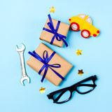 Father`s day concept card with man`s work tool on blue background and gifts boxes wrapped in kraft paper and tied with blue bow. Top view stock photography