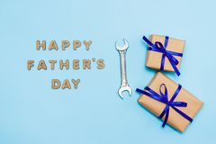 Father`s day concept card with man`s work tool on blue background and gifts boxes wrapped in kraft paper and tied with blue bow. Top view royalty free stock photography