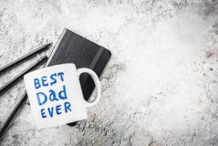 Father`s Day concept. Background for congratulating cards with a cup with the inscription Best Father ever, business notebook and pencils. copy space top view Stock Photos