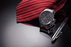 Father& x27;s Day concept image. Man& x27;s watch, pen and red tie folded on black gradient background. Stock Photos