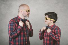 Father`s day,father and son with tie and sunglasses. Against gray background royalty free stock images