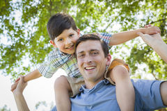 Father's Day Fun - Son Rides Piggyback with his Dad. Mixed Race Father and Son Playing Piggyback Together in the Park Royalty Free Stock Images