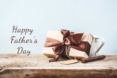 Father`s Day. Gift box with a tag and coffee cup on a wooden background Copy space Text royalty free stock image