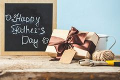 Father`s Day. Gift box with a tag , tools and coffee cup on a wooden background Copy space Text. royalty free stock photo