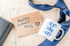 Father`s Day gift concept. Greeting card background, gift box, tie decoration, mug with inscription Best Dad Ever, notebook, top view Royalty Free Stock Images