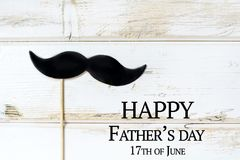 Father`s Day Greeting Card with Black Moustache. Happy Father`s Day greeting card with Black Moustache on a White Wooden Background.17th of June royalty free stock photography