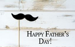 Father`s Day Greeting Card with Black Moustache. Happy Father`s Day greeting card with Black Moustache on a White Wooden Background.17th of June royalty free stock photo