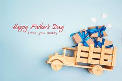Father`s Day greeting message with wooden toy truck with gift bo. X in the back on blue background. Happy fathers day concept royalty free stock images