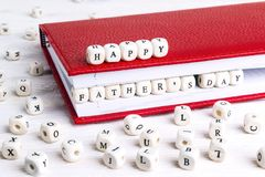 Father`s Day greeting message written in wooden blocks in red no. Tebook on white wooden table. Fathers day background stock photos
