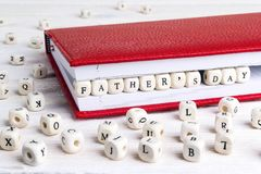 Father`s Day greeting message written in wooden blocks in red no. Tebook on white wooden table. Fathers day background stock image