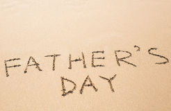 Father's Day hand written in the sandy beach Royalty Free Stock Photos