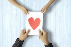 Dad receives greeting card. Father`s Day. Hands of dad receiving a greeting card with heart symbol from his child Royalty Free Stock Photo