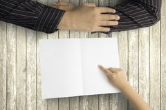 Child and dad with empty greeting card. Father`s Day. Hands of little child pointing an empty greeting card for his father above a wooden table Royalty Free Stock Photo