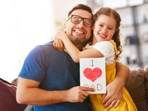 Father`s day. Happy family daughter hugging dad and laughs royalty free stock image