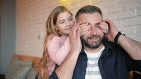 Father`s day. Happy Family Daughter Hugging Dad And Laughs on Holiday. She Covers His Eyes From Back. They Have a Lot of. Fun Together. HD, Fathers Day, Indoors stock video footage
