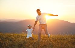 Father`s day. Happy family father and toddler son playing and la. Ughing on nature at sunset Royalty Free Stock Images