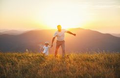 Father`s day. Happy family father and toddler son playing and la. Ughing on nature at sunset Stock Photo