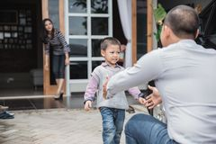 Welcoming daddy home after work. Father`s day. Happy family son running and hugging dad after work royalty free stock image
