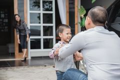 Welcoming daddy home after work. Father`s day. Happy family son running and hugging dad after work stock photo
