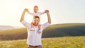 Father`s day. Happy family father and toddler son playing and l. Aughing on nature at sunset stock photos