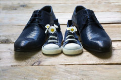 Father's day, kids sneakers with a bouquet of daisies standing b. Etween daddy's black men shoes on rustic gray wood, copy space Stock Photo