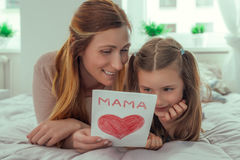Father´s day mother´s day. Girl surprising parents with greeting card at home stock image