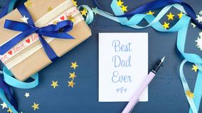 Father`s Day overhead with decorated borders on dark blue wood table. Happy Father`s Day overhead with decorated borders, gift and greeting card on dark blue Stock Photography