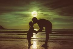 Father`s day. Silhouette side view of loving child kissing her f. Father`s day. Silhouette of loving child kissing her father. Family enjoying and relaxing on Stock Image